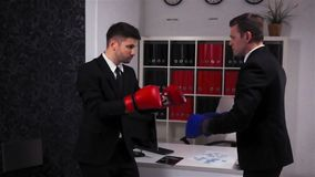 Two businessmen boxing in office room. Two young handsome attractive businessmen boxing in office room. Red and blue gloves. Super slow motion shot. Competition stock video