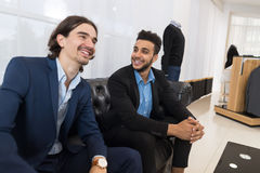 Two Young Handsome Business Man Sitting On Coach In Retail Store Speaking Shopping Royalty Free Stock Photo