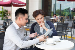 Two young handsome businessmen in casual clothes smiling, talking in coffee shop. royalty free stock image