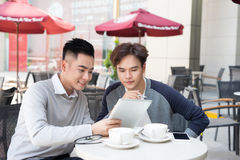 Two young handsome businessmen in casual clothes smiling, talking in coffee shop. royalty free stock images