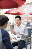 Two young handsome businessmen in casual clothes smiling, talking, drinking coffee while working in office royalty free stock photography