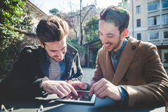 Two young handsome businessmen using tablet Stock Photos