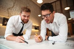 Two young handsome businessmen working on a business plan. While standing over desk with graph indoors Royalty Free Stock Photo