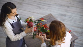 Two young handsome chef florists work at flowers fruit shop making fruit and vegetable bouquet. Top view of two young handsome chef florists work at flowers stock footage