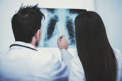 Two young handsome doctors are looking at roentgen in medical office. Back view Royalty Free Stock Photos