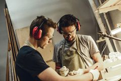 Young craftsmen drawing in workshop royalty free stock photos