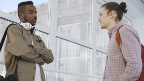 Two young handsome guys are standing in big glassy college corridor communicating in positive way and smiling. Afro. Two young handsome guys are standing in big stock footage