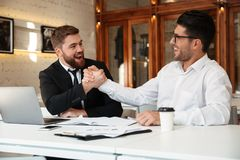 Two young handsome happy business partners in formalwear shaking. Two young handsome satisfied business partners in formalwear shaking hands in the office Stock Photo