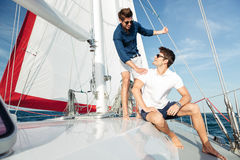 Two young handsome happy men standing on the yacht Stock Photo
