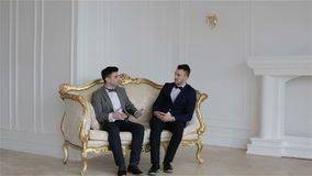 Two young handsome man sitting on a vintage sofa. Two young handsome man sitting on a vintage sofa and discussing business stock video footage