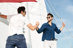 Two young handsome men greeting standing on the yacht Royalty Free Stock Photos