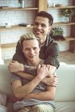 Two young handsome men hugging at home royalty free stock photo