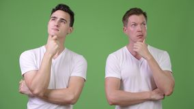 Two young handsome men thinking together. Studio shot of two young handsome men together against chroma key with green background stock video footage