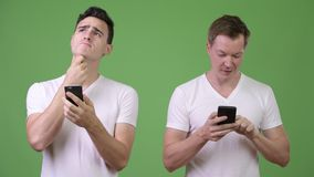 Two young handsome men thinking while using phones together. Studio shot of two young handsome men together against chroma key with green background stock video