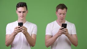 Two young handsome men using phones together. Studio shot of two young handsome men together against chroma key with green background stock video footage