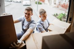 Two young handsome smiling movers wearing uniforms are unloading the van full of boxes. House move, mover service royalty free stock photo