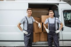 Two young handsome smiling workers wearing uniforms are standing next to the van full of boxes. House move, mover. Service royalty free stock image