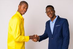 Two young happy African businessmen shaking hands together stock photos