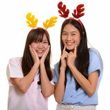 Two young happy Asian teenage girls smiling and posing ready for. Christmas royalty free stock image