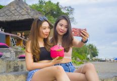Two young happy and attractive Asian Chinese and Korean women hanging out , girlfriends enjoying holidays trip in tropical resort stock photos