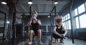 Two young happy beautiful athletic Caucasian women exercising together in large gym jumping on big blocks slow motion. Motivation concept, woman training with stock video footage
