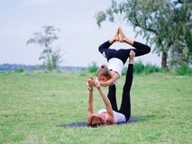 Two young happy beautiful barefoot girls doing yoga in city park. Contact yoga together Stock Photography