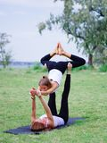 Two young happy beautiful barefoot girls doing yoga in city park. Contact yoga together Stock Photos