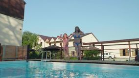 Two young happy blondes run up to pool and synchronously dive into it. Slowmo stock video