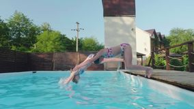 Two young happy blondes synchronously dive into outdoor pool. Slowmo stock video
