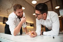 Two young happy businessmen working on a business plan. While standing over desk with graph indoors Royalty Free Stock Photography