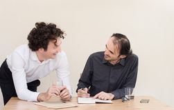 Two young happy Caucasian colleagues at the table in the office with light background. stock image
