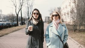 Two young happy Caucasian ladies walking together. Girlfriends chatting in the street. Business women meeting outside. Two young happy Caucasian females walking stock footage