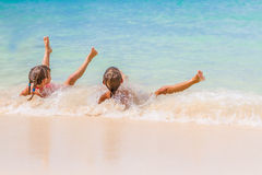 Two young happy children - girl and boy - having fun in water, t Royalty Free Stock Image