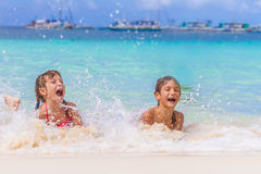 Two young happy children - girl and boy - having fun in water, t Royalty Free Stock Photos