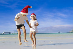 Two young happy children in santa hats on tropical beach Stock Photos