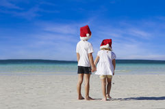 Two young happy children in santa hats on tropical beach Royalty Free Stock Images