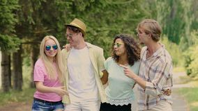 Two young happy couples embracing outdoors, singing and dancing in slow motion. Stock footage stock video
