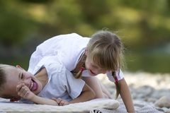 Two young happy cute blond laughing children, boy and girl, brother and sister having fun on pebbled beach on blurred bright royalty free stock image