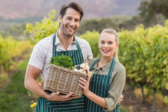 Two young happy farmers holding a basket of vegetables Royalty Free Stock Images