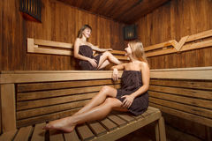 Two young and happy females in sauna. Two young and happy females sitting on the bench in sauna Royalty Free Stock Photo