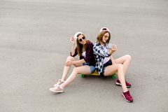 Two young happy girl friends in hipster outfit sitting together on longboard and making selfie on phone stock photos