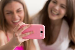 Two young happy girlfriends taking selfie with smart phone. royalty free stock images