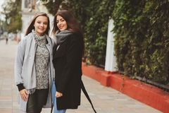 Two young happy girlfriends walking on city streets in casual fashion outfits Stock Images