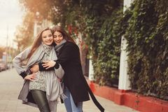 Two young happy girlfriends walking on city streets in casual fashion outfits Royalty Free Stock Image