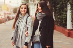 Two young happy girlfriends walking on city streets in casual fashion outfits Stock Photography