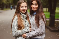 Two young happy girlfriends walking on city streets in casual fashion outfits Stock Image