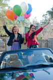 Two young happy girls with air balloons in cabrio Stock Images