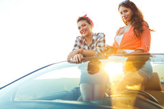 Two young happy girls having fun in the cabriolet outdoors Royalty Free Stock Photos