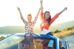 Two young happy girls having fun in the cabriolet outdoors Stock Images