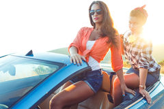 Two young happy girls having fun in the cabriolet outdoors. Summer vacation concept Royalty Free Stock Photo